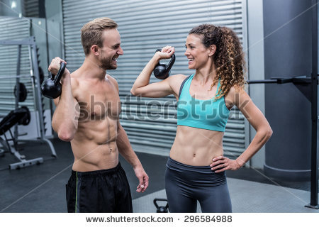 stock-photo-muscular-couple-discussing-together-while-lifting-kettlebells-296584988